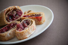 Plate of strudel. Sweet cherry strudel of puff pastry; two slices on plate royalty free stock photography