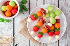 Plate of summer fruit skewers on rustic white wood. Plate of delicious summer fruit skewers with melon, cheese and prosciutto on a rustic white wood background stock images