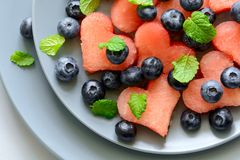Plate with summer watermelon salad with blueberry and mint leaves on gray plate. Healthy eating concept. Top view royalty free stock photography
