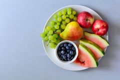 Plate with summer fruits: watermelon, blueberry,apples,pear and grape on white plate. Healthy eating concept. Top view. Copy space.  royalty free stock photography