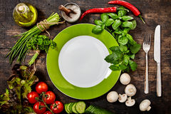 Plate Surrounded by Fresh Herbs and Vegetables Stock Image