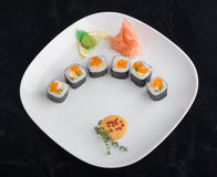 Plate of sushi. Sushi on white plate against black background Royalty Free Stock Photos