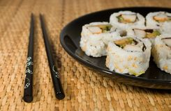Plate of sushi - california rolls. Plate of california rolls on natural wicker background Royalty Free Stock Images
