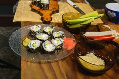 A plate with sushi roles in the kitchen, cooked by a woman`s chef with her own hands royalty free stock image