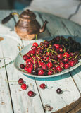 Plate of sweet cherries on light blue wooden table. Plate of fresh ripe sweet cherries on rustic light blue wooden garden table, selective focus. Summer food royalty free stock images