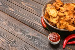 Plate of sweet potato chips, sauce and hot pepper on wooden table. Space for text stock photo