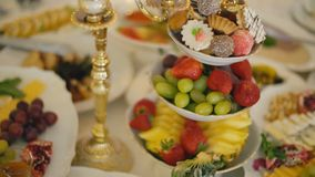 A plate of sweets and fruit. A plate with sweets and fruit on a table with various foods stock video footage