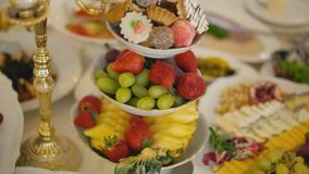 A plate of sweets and fruit. A plate with sweets and fruit on a table with various foods stock footage