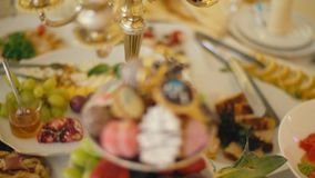 A plate of sweets and fruit. A plate with sweets and fruit on a table with various foods stock video