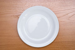 Plate on table. White plate on the wood background Royalty Free Stock Photography