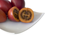 A plate of Tamarillos. Tamarillos on a plate, isolated on white royalty free stock image