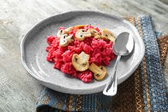 Plate of tasty beetroot risotto with mushrooms on table. Closeup Royalty Free Stock Image
