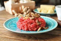 Plate of tasty beetroot risotto with mushrooms on table. Closeup Stock Images