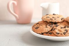 Plate with tasty chocolate chip cookies and blurred cup of milk on gray background stock photos