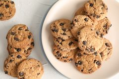 Plate with tasty chocolate chip cookies on gray background stock photography