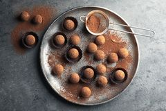 Plate with tasty chocolate truffles on grey background. Flat lay royalty free stock photo