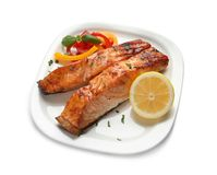 Plate with tasty cooked salmon. On white background Stock Photo