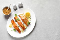 Plate with tasty cooked salmon served for dinner. On table, top view Stock Photos