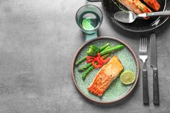 Plate with tasty cooked salmon served for dinner. On table, top view Stock Images