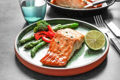 Plate with tasty cooked salmon on tabe, Royalty Free Stock Images