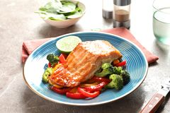 Plate with tasty cooked salmon on table Royalty Free Stock Photos