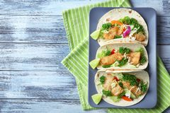 Plate with tasty fish tacos. On table royalty free stock photo