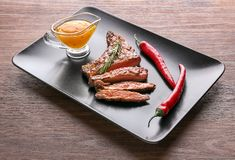 Plate with tasty grilled steak, chili and sauce on wooden table royalty free stock photography