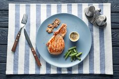 Plate with tasty grilled steak, garnish and sauce on wooden table stock photo