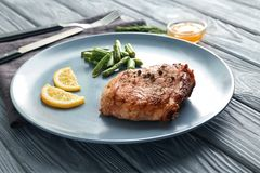 Plate with tasty grilled steak and green beans on wooden table royalty free stock photos