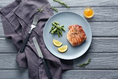 Plate with tasty grilled steak and green beans on wooden table stock images