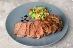 Plate with tasty grilled steak on grey background royalty free stock photography