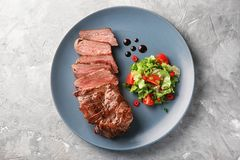 Plate with tasty grilled steak on grey background stock photo