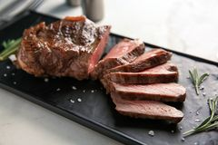 Plate with tasty grilled steak on light background royalty free stock photos