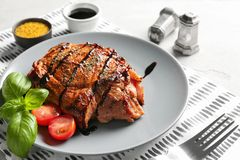 Plate with tasty grilled steak and sauces on table royalty free stock image