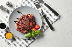 Plate with tasty grilled steak and sauces on table stock image