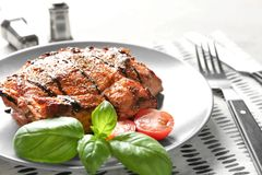 Plate with tasty grilled steak on table royalty free stock photos