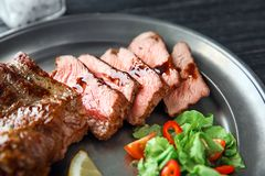 Plate with tasty grilled steak on table, closeup royalty free stock images