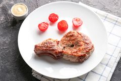 Plate with tasty grilled steak and tomatoes on table stock photos