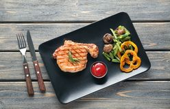 Plate with tasty grilled steak, vegetables and sauce on wooden table royalty free stock photo