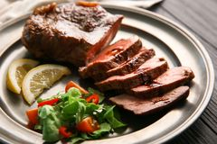 Plate with tasty grilled steak on wooden background, closeup royalty free stock photography