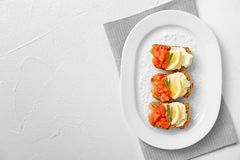 Plate of tasty sandwiches with fresh sliced salmon fillet. On table, top view stock image