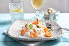 Plate with tasty seafood risotto. On table Royalty Free Stock Photos