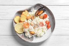 Plate with tasty seafood risotto. On table Royalty Free Stock Photography