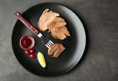 Plate with tasty steak and some ingredients. On kitchen table Royalty Free Stock Photography