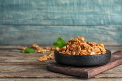 Plate with tasty walnuts on wooden table. Space for text stock image