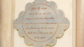 Plate with the Text in The Form of Flower. A Plate in the Form of a Flower Hangs on the Wall. The Text in it is Written in Arabic. The Inscription Was Made a stock footage