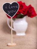 The plate with the text of i love you in the form of heart against red roses Stock Photo
