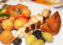 On a plate there is a chicken shashlik with potatoes, olives, ol royalty free stock photography