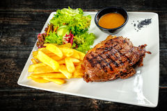 Plate with thick juicy stake, bowl of steaming red sauce, golden french fries. stock photo