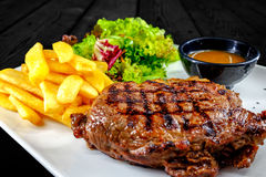 Plate with thick juicy stake, bowl of steaming red sauce, golden french fries. stock photos